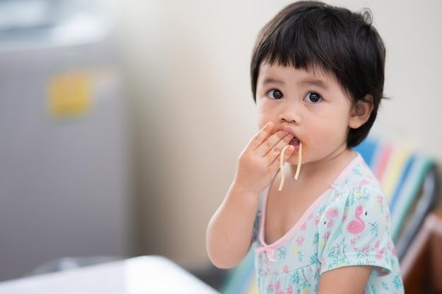 Słodkie dziecko azjatyckie jedzenie spaghetti w jadalni