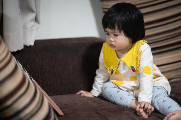 Słodkie dziecko azjatyckie, patrząc na telefon komórkowy i siedząc na kanapie