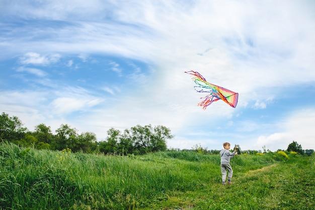 Słodkie dziecko bawi się z zewnątrz kolorowy latawiec