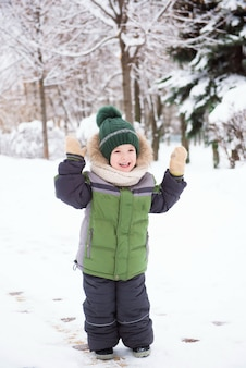 Słodkie dziecko bawiące się w śniegu. zajęcia zimowe dla dzieci.