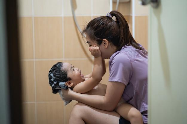 Słodkie dziecko bierze prysznic z mamą w toalecie
