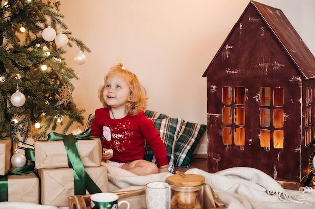 Słodkie dziecko blondynka z ptasie mleczko w ręku siedzi pod udekorowaną choinką i podziwiając ją.