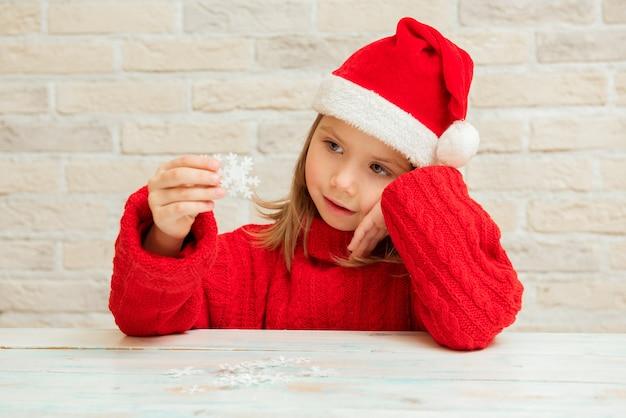 Słodkie dziecko dziewczyna siedzi w czerwonym kapeluszu świętego mikołaja, czekając na wakacje, boże narodzenie, nowy rok