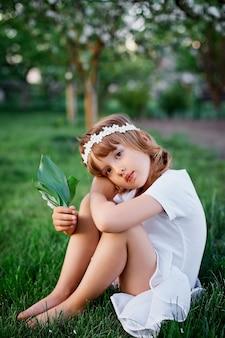 Słodkie dziecko dziewczynka 5-6 lat trzyma kwiat siedzi w kwitnącym wiosennym ogrodzie, ubrana w białą sukienkę i kwiatowy wianek na zewnątrz, zbliża się sezon wiosna.