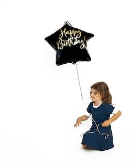 Słodkie dziecko dziewczynka kaukaski 4-5 lat siedzi szczęśliwie z balonem żelowym czarny z napisem happy birthday. zdjęcie w studio na białym tle