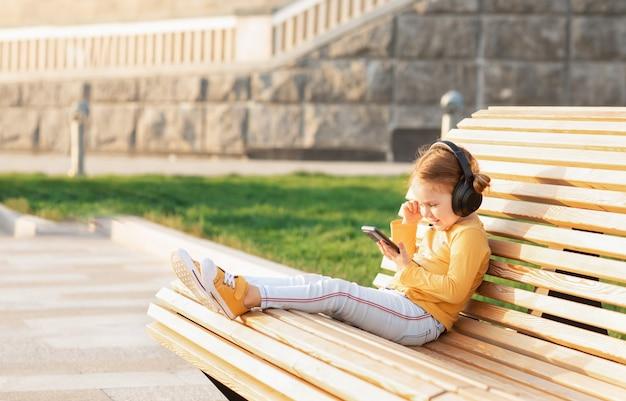 Słodkie dziecko dziewczynka korzystających w parku podczas słuchania muzyki z telefonu komórkowego i słuchawek. edukacja online, styl życia, koncepcja komunikacji online technologii. koniec kwarantanny. koronawirus się skończył