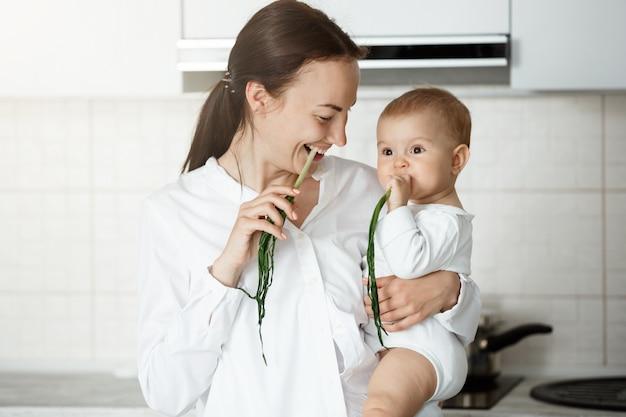 Słodkie dziecko i jej matka jedzenie zielonej cebuli