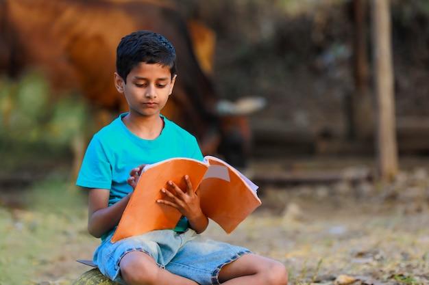 Słodkie dziecko indyjski czytając swoją książkę w szopie bydła