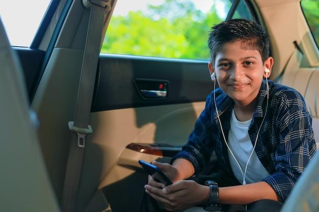 Słodkie dziecko indyjskie siedzi w samochodzie i korzysta z gadżetu smartfona i słuchawek