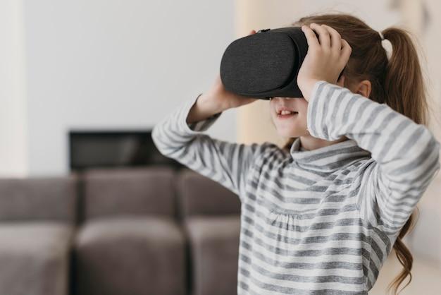 Słodkie dziecko korzystające z widoku z boku zestawu słuchawkowego wirtualnej rzeczywistości