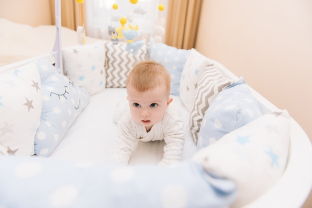 Słodkie dziecko leży w białym okrągłym łóżku. lekka szkółka dla małych dzieci.