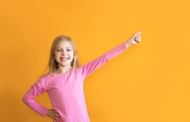 Słodkie dziecko na pomarańczowej ścianie, 6-8 lat, dziewczyna w różowych ubraniach uśmiecha się, wskazuje na określone miejsce