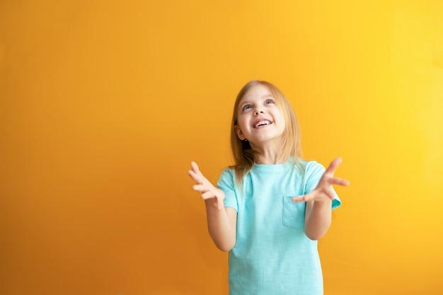 Słodkie dziecko na pomarańczowej ścianie, 6-8 lat, dziewczynka łapie coś lub jest gotowe złapać spadanie z góry