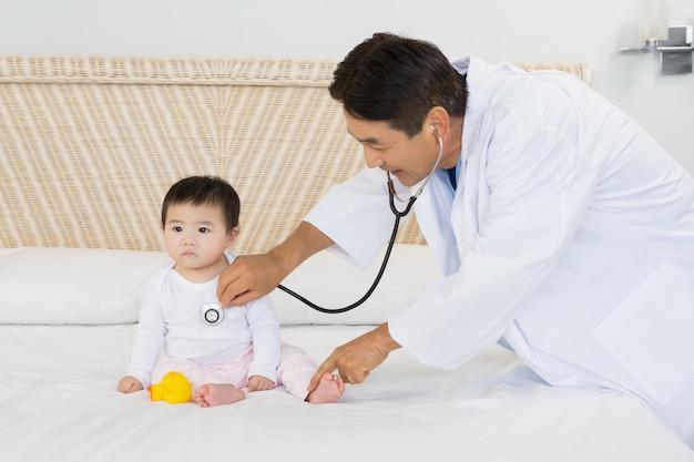 Słodkie dziecko odwiedzane przez lekarza na łóżku