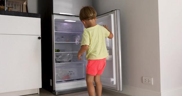Słodkie dziecko otwiera lodówkę wygląda na butelkę