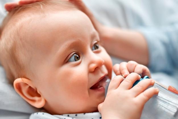 Słodkie dziecko pije mleko z butelki dla niemowląt, patrząc na swoją mamę. matka karmienia niemowlęcia syna z butelki. mały chłopiec pije mleko z butelki w domu.