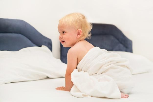 Słodkie dziecko pod białym ręcznikiem siedzi na łóżku