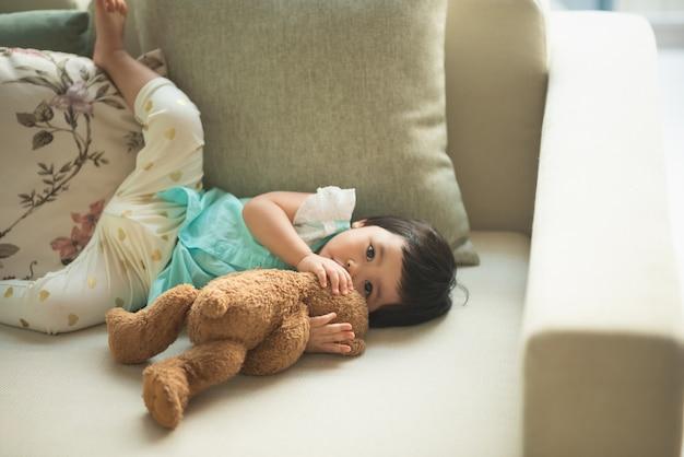 Słodkie dziecko przytulanie misia odpoczywa na sofie w toalecie