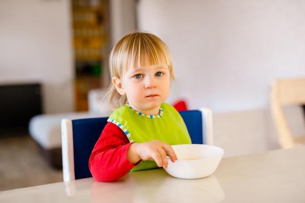 Słodkie dziecko siedzi na wysokim krzesełku dla dzieci i samodzielnie je warzywa w białej kuchni.