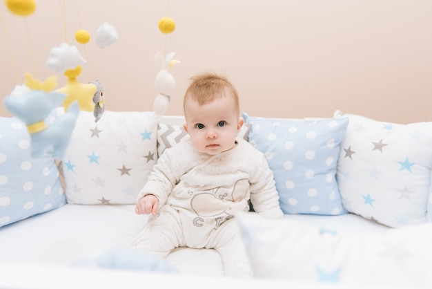Słodkie dziecko siedzi w białym okrągłym łóżku. lekka szkółka dla małych dzieci. zabawki do łóżeczka niemowlęcego. uśmiechnięte dziecko bawiąc się mobile z filcu w słonecznej sypialni.