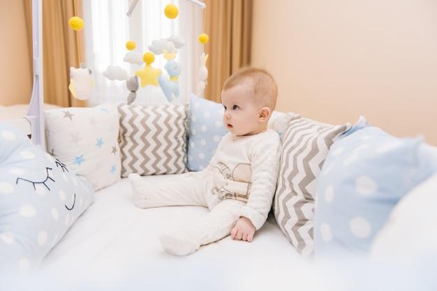 Słodkie dziecko siedzi w białym okrągłym łóżku. lekka szkółka dla małych dzieci. zabawki do łóżeczka niemowlęcego. uśmiechnięte dziecko grając z mobile filcu w słonecznej sypialni.