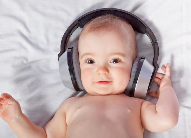 Słodkie dziecko słucha muzyki przez słuchawki. zbliżenie.