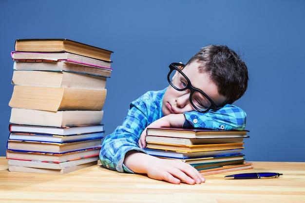 Słodkie dziecko śpi przy biurku w szkolnej bibliotece