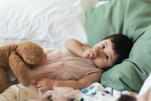 Słodkie dziecko ssie palec i śpi na łóżku