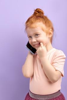 Słodkie dziecko trzymające telefon komórkowy, uśmiechające się, mające z kimś miłą rozmowę