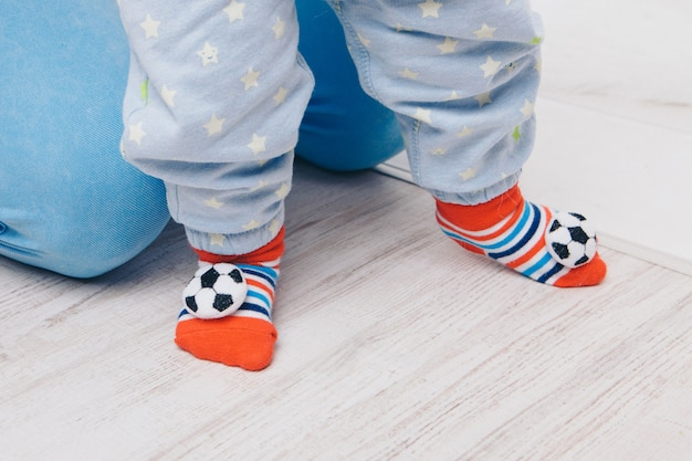 Słodkie dziecko uczy się chodzić i stawiać pierwsze kroki. mama trzyma rękę. stopy dziecka z bliska, miejsce, skarpetki z kulkami