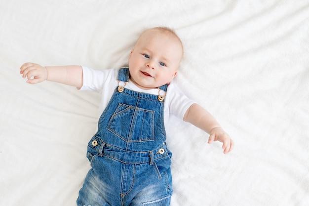 Słodkie dziecko uśmiecha się leżąc na białym łóżku w domu w dżinsowym garniturze