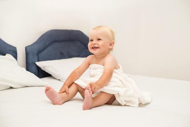 Słodkie dziecko uśmiecha się pod białym ręcznikiem i siedzi na łóżku