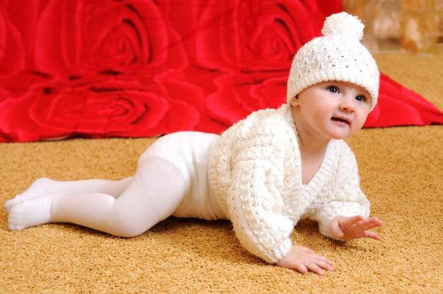 Słodkie dziecko w białe ubrania z dzianiny