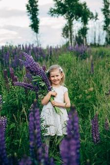 Słodkie dziecko w białej sukni w polu łubinu