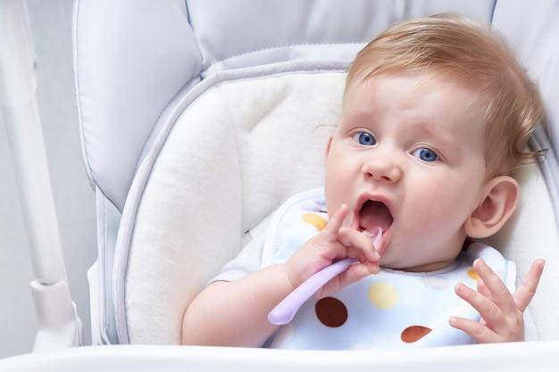 Słodkie dziecko w foteliku zjada owsiankę. pierwsza przynęta z bliska