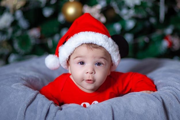 Słodkie dziecko w garniturze mikołaja w pobliżu choinki, nowy rok