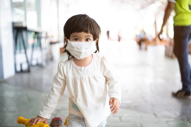 Słodkie dziecko w masce chirurgicznej, koncepcja ochrony przed koronawirusem covid-19