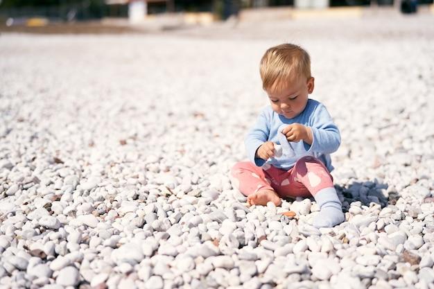 Słodkie dziecko w niebieskiej bluzce i czerwonych spodniach siedzi na kamienistej plaży, pochylając głowę i trzymając kamyki