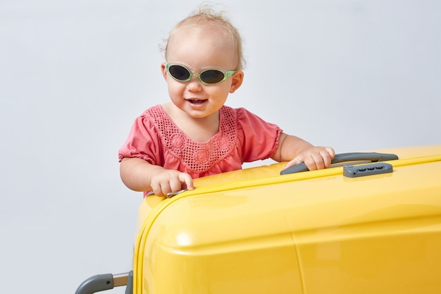 Słodkie dziecko w okularach przeciwsłonecznych stoi obok walizki. pojęcie rekreacji i podróży.