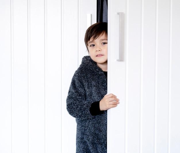 Słodkie dziecko w puszystej piżamie stojącej za szafą, mały chłopiec z uśmiechniętą twarzą, trzymając białe drzwi, dziecko bawiące się w chowanego i chowające się w szafie