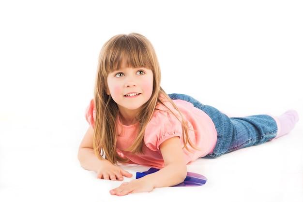 Słodkie dziecko w różowym ubranku leży na brzuchu podczas gry