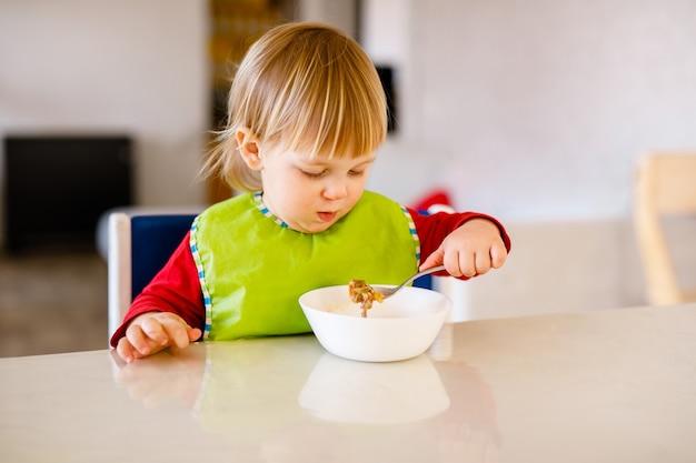 Słodkie dziecko w wieku 1,4 lat siedzi na wysokim krzesełku i je samotnie warzywa w białej kuchni.