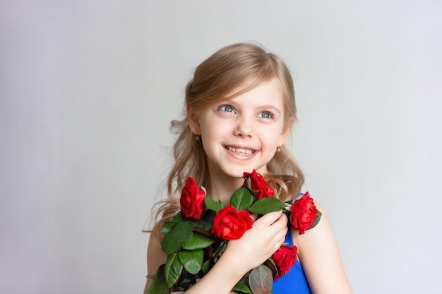 Słodkie dziecko w wieku 7-8 lat, córka matki, śliczna dziewczynka, dziewczynka o blond włosach i czerwonych róż