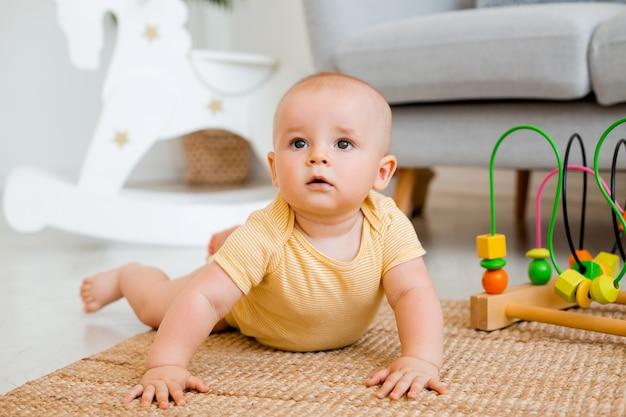 Słodkie dziecko w żółtym body bawi się zabawką edukacyjną
