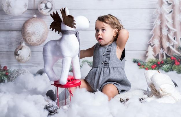 Słodkie dziecko wygląda na zaskoczonego małym reniferem.