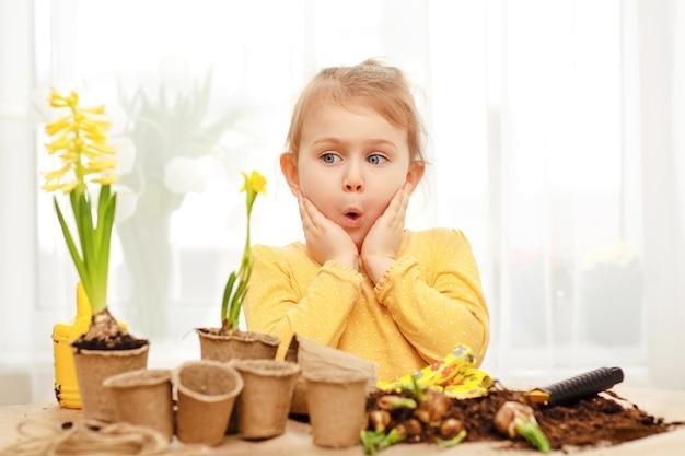 Słodkie dziecko wygląda na zaskoczonego żółtym kwiatkiem. baw się, ucząc się i zajmując się ogrodnictwem w domu, przedszkolu, klasie przedszkolnej