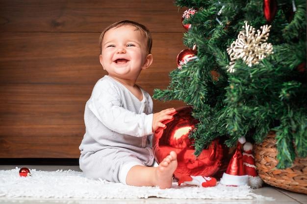 Słodkie dziecko z choinką. szczęśliwe dziecko siedzi w pobliżu jodły i trzyma bombkę i uśmiecha się