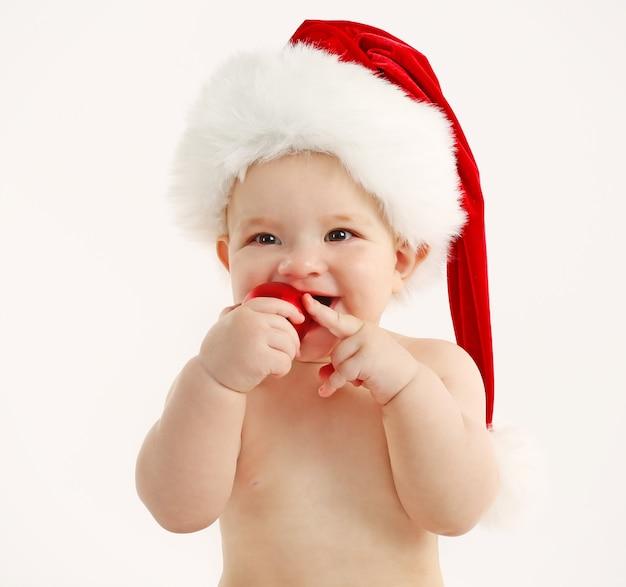 Słodkie dziecko z czapką świętego mikołaja i ozdób choinkowych na białym tle