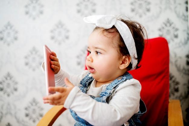 Słodkie dziecko z telefonem komórkowym siedzącym na krześle.