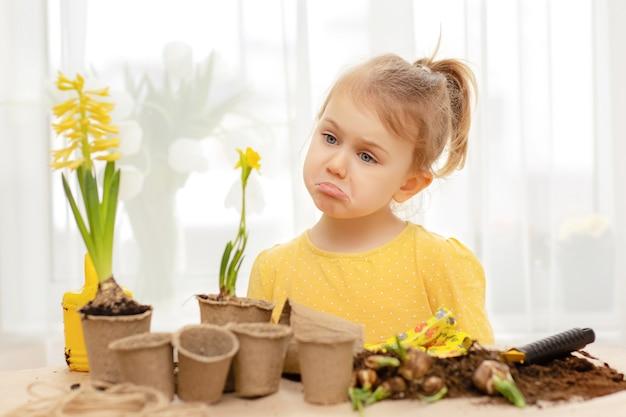 Słodkie dziecko ze smutkiem patrzy na żółty kwiatek. opieka nad roślinami. baw się, ucząc się i zajmując się ogrodnictwem w domu, przedszkolu, klasie przedszkolnej